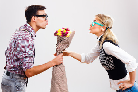 Young nerdy man is giving a bouquet of flowers to his nerdy lady. Stock Photo