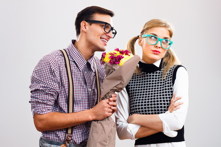he and she: Nerdy man is giving a bouquet of flowers to his girlfriend,he had made a mistake and he is hoping that she will forgive him. Stock Photo