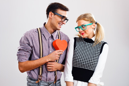 Nerdy man is about to give a red heart to his nerdy lady to show that he loves only her.