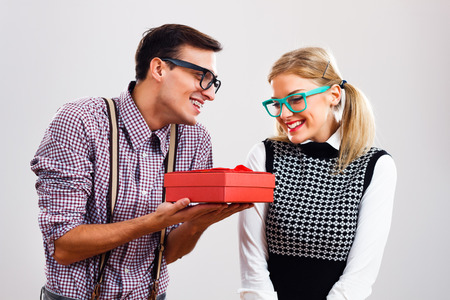 Nerdy man is giving a present to his nerdy lady.