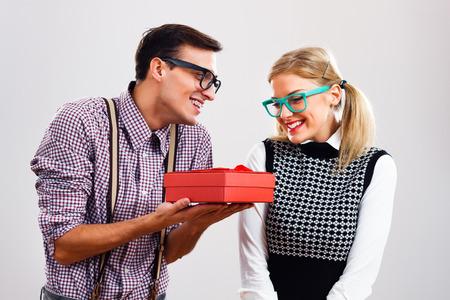 Uomo Nerdy sta dando un regalo alla sua donna nerd. Archivio Fotografico