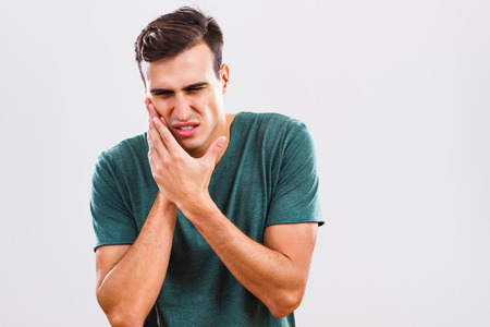 man mouth: Young man is having toothache.