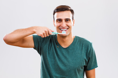 Portrait of man with braces holding toothbrush.