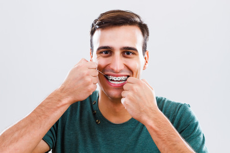 Photo of young man with braces using dental floss.