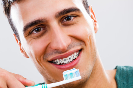 one adult: Portrait of man with braces holding toothbrush.
