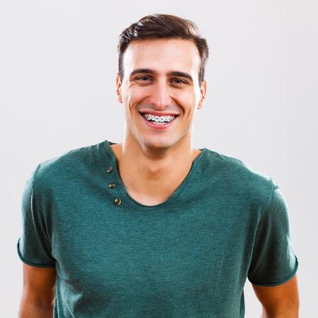 appareil dentaire: Portrait de contenu jeune homme avec des accolades.