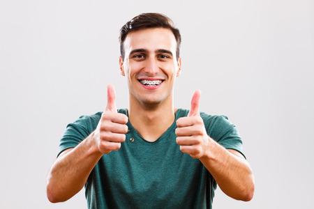 親指を現してブレース付きコンテンツの若い男の写真。