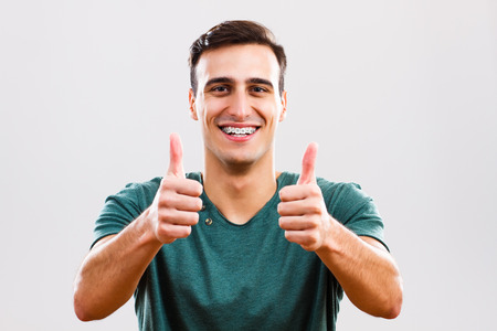 looking up: Photo of content young man with braces showing thumbs up. Stock Photo