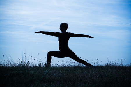 intentionally: A silhouette of a woman practicing yoga,intentionally toned image.
