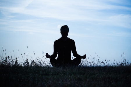 A silhouette of a woman meditating ,intentionally toned image.