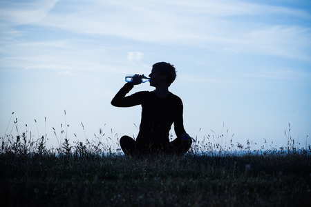 people drinking water: A silhouette of a woman drinking water after exercise,intentionally toned image. Stock Photo