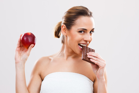 Beautiful woman wants to have one more bite of chocolate before she starts to eat healthy. photo