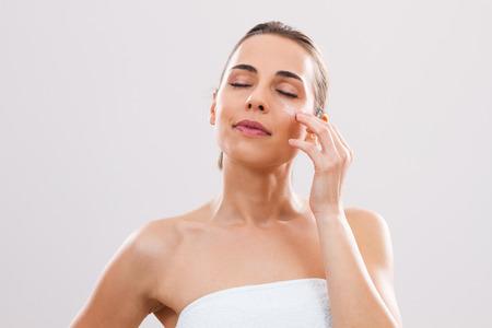 美しい女性は、彼女の顔に化粧水です。