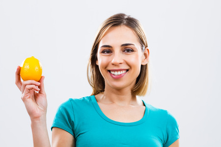 Beautiful woman is holding lemon in her hand.
