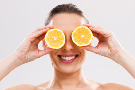 close up food: Beautiful woman is covering her eyes with slices of lemon.