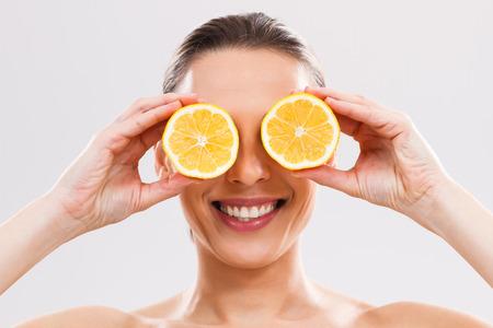 vida sana: Hermosa mujer est� cubriendo sus ojos con rodajas de lim�n. Foto de archivo