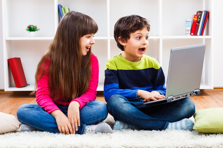 Cute little girl and little boy are using laptop. Stock Photo