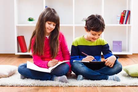 Cute little girl and little boy are doing their homework.