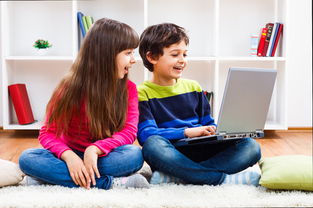 Cute little girl and little boy are using laptop. Banco de Imagens