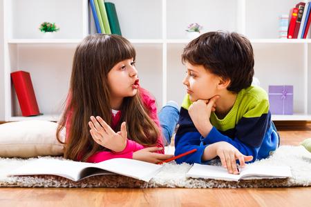 dos personas platicando: Ni�a y ni�o peque�o han decidido tomar un descanso de la tarea y ahora est�n teniendo una conversaci�n.