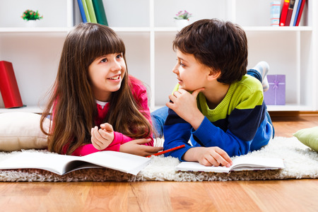 Little girl and little boy have decided to take a break from homework and now they are having conversation.