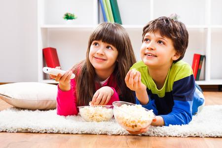 Dzieci: Mała dziewczynka i mały chłopiec cieszyć jeść popcorn i oglądanie telewizji w domu.
