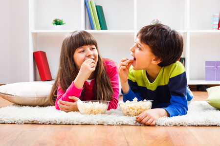 eating popcorn: Little girl and little boy enjoy eating popcorn at home.