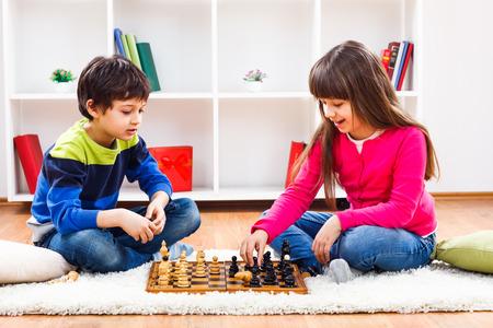 少年と少女は、家でチェスを遊んでいます。