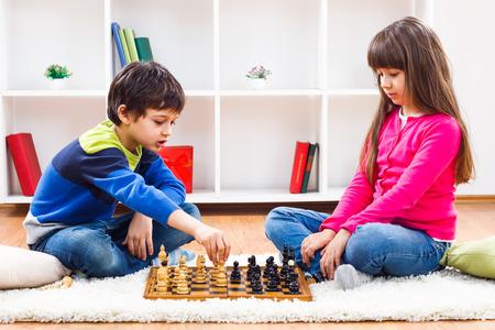 niños sentados: Niño pequeño y niña están jugando al ajedrez en casa.