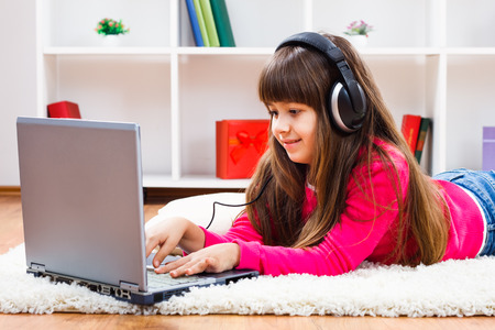 Cute little girl with headphones is using laptop at her home.