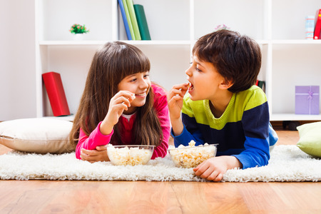 Little girl and little boy enjoy eating popcorn at home.