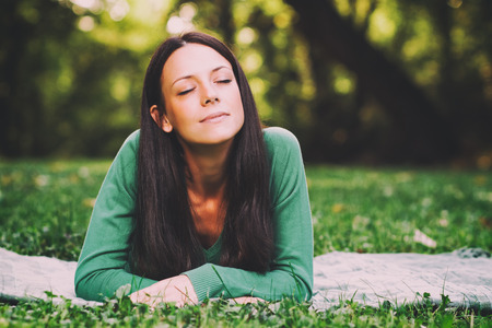 自然に横たわっていると、何かを考えての美しい若い女性は意図的にイメージをトーンダウンしました。 写真素材
