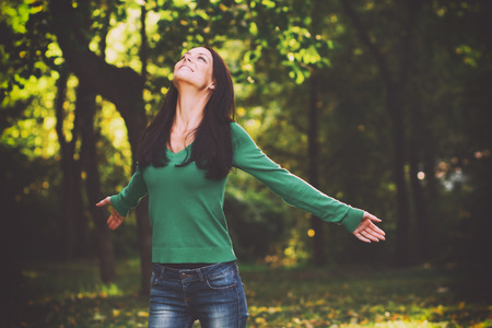 intentionally: Beautiful young woman enjoys in nature.,intentionally toned image.