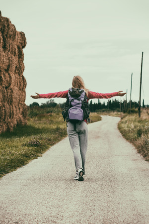 feeling up: Blonde woman waist up her arms while she is standing in nature,she is feeling carefree,intentionally toned image.