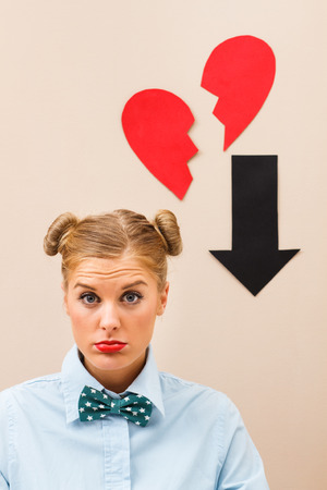 20 24 years old: Cute geek girl is sad  because someone has broken her heart. Stock Photo