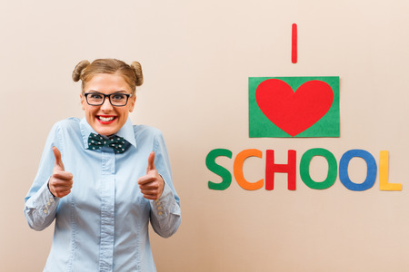 20 24 years old: Cute geek girl is giving thumbs up for school.