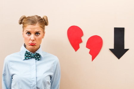heart problems: Cute geek girl is sad  because someone has broken her heart. Stock Photo