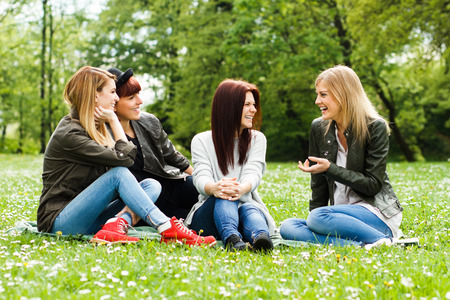 adult group: Four young girls sitting in the park and talking about something.