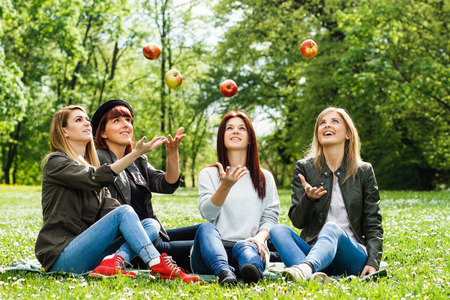 four person only: Happy girls throwing apples in the park