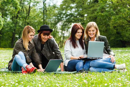 4 人の若い女の子公園で座っているとラップトップを使用して。