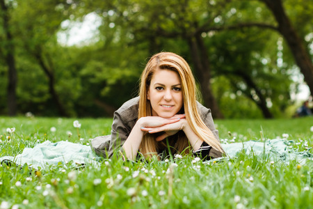 girl lying down: Cute young girl lying down in nature and looking at camera.