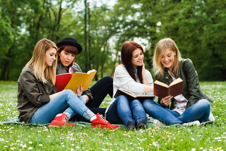 four person only: Young girls sitting in the park and learning.