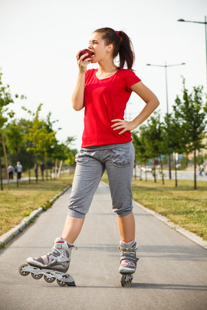 healthy snack: Cute young girl is having healthy snack after roller skating. Stock Photo