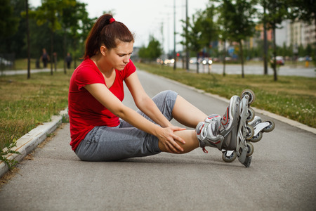 Young girl in roller skates fell down and now she feels pain in her leg.