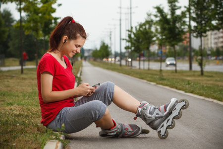 Portrait of cute young girl in roller skates resting and  using phone.