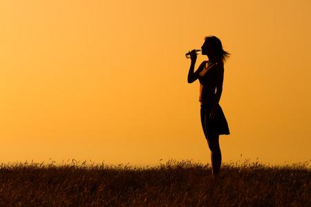 tomando agua: Una silueta de una mujer agua potable.