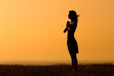 Silhouette di una donna meditando. Archivio Fotografico