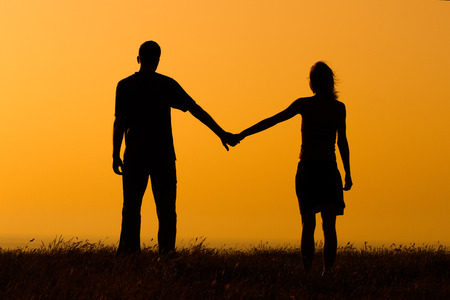people holding hands: Couple in love enjoy watching sunset together Stock Photo