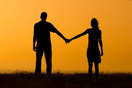 holding hands: Pareja de enamorados disfrutar viendo la puesta de sol juntos