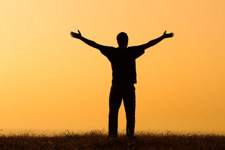幸せな男は、日没で楽しんでいます。 写真素材